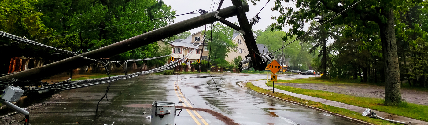 fallen electrical distribution tower on winding neighborhood road after a storm