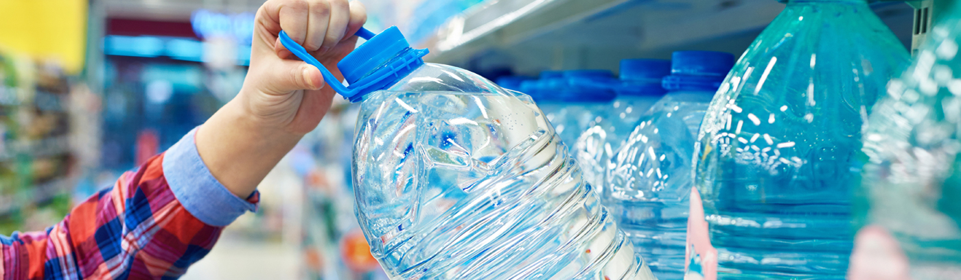 Single hand reaching for one blue-capped water jug inside the isle of a convenience store