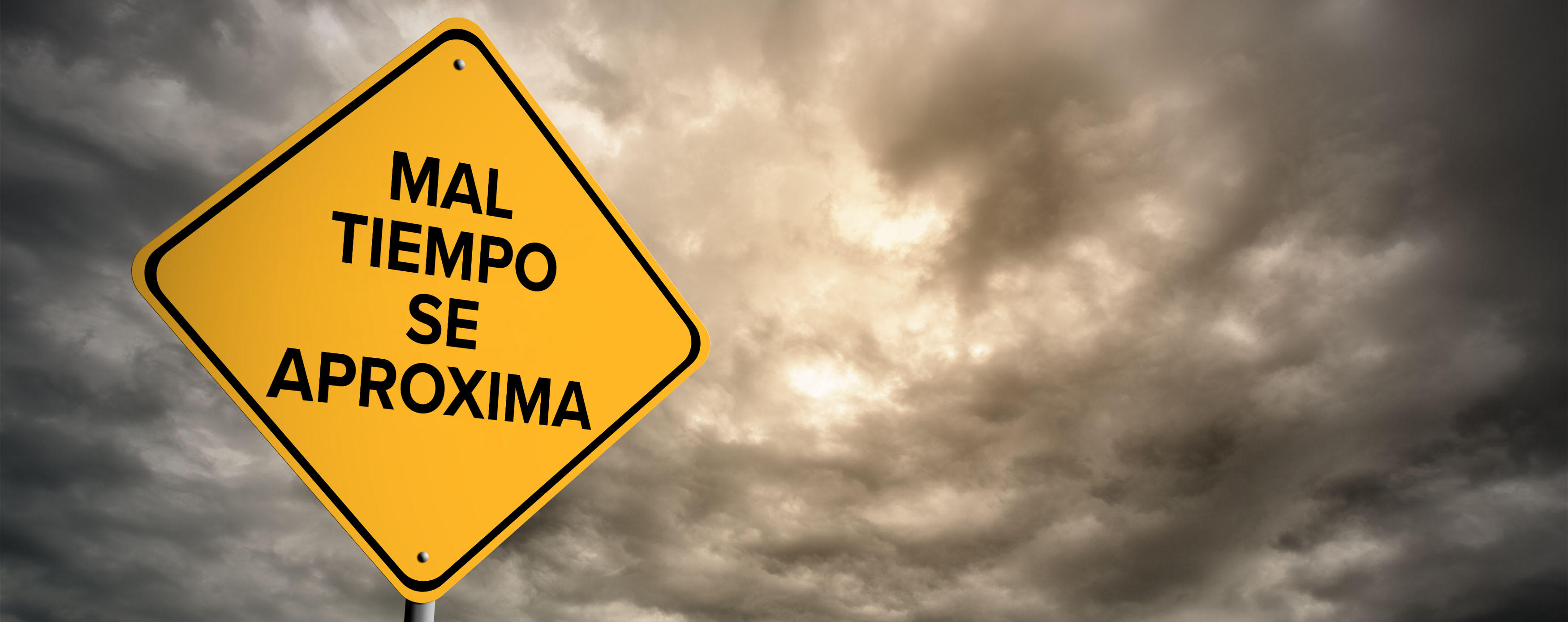 Dark clouds behind yellow emergency sign for stormy weather ahead